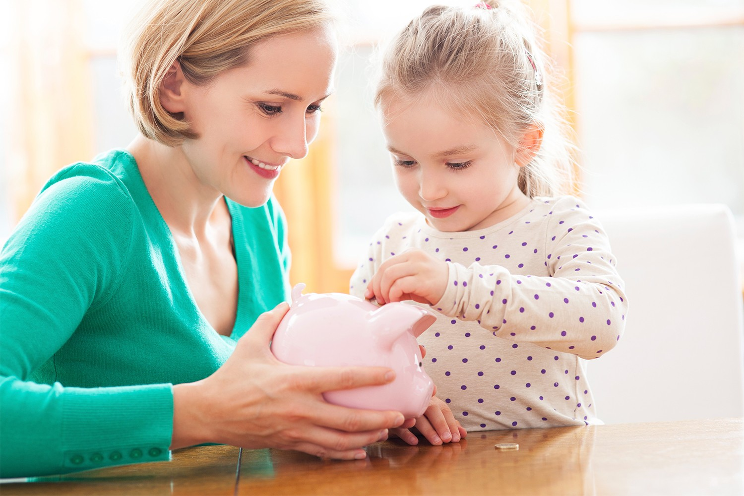 monther and daughter putting coins in piggy bank