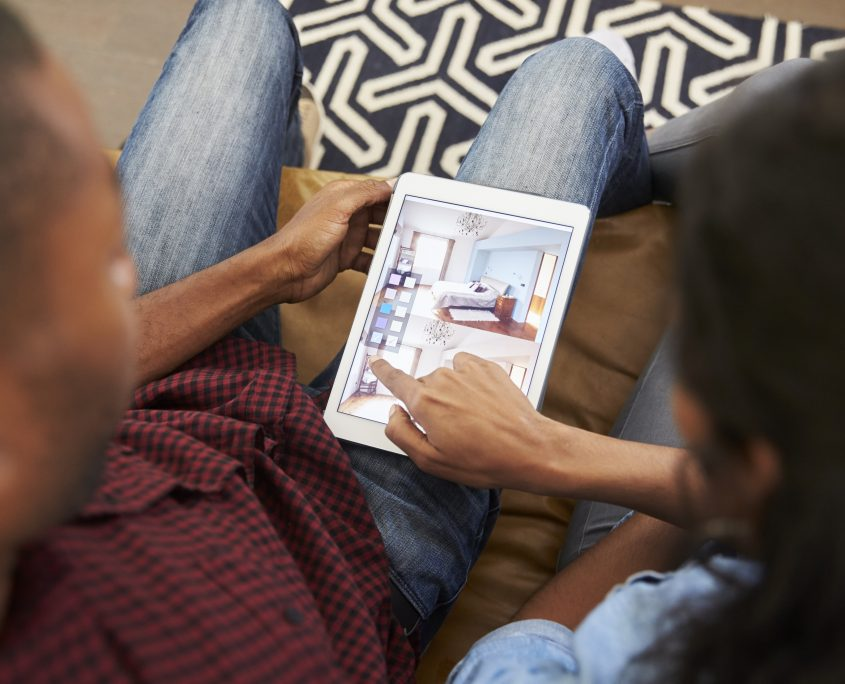 couple sitting on sofa looking at home design app